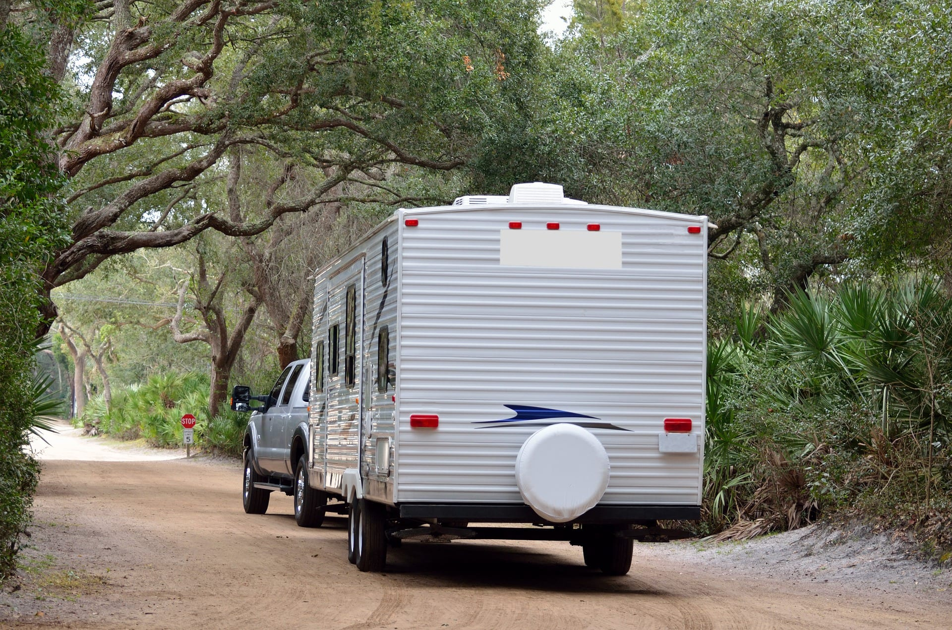 The back of an RV trailer being pulled by a pickup truck on a dirt road