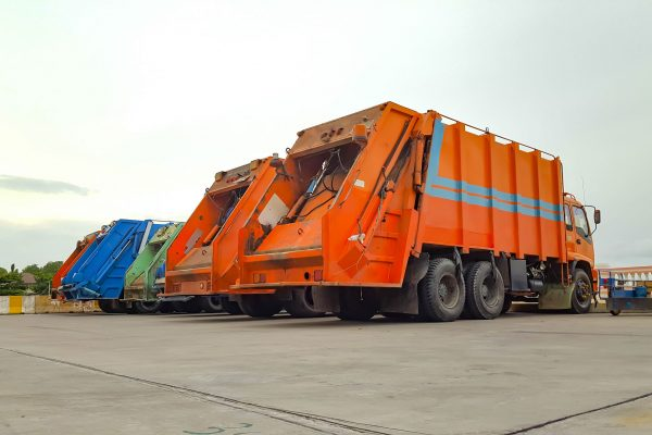 The backs and sides of multiple garbage trucks